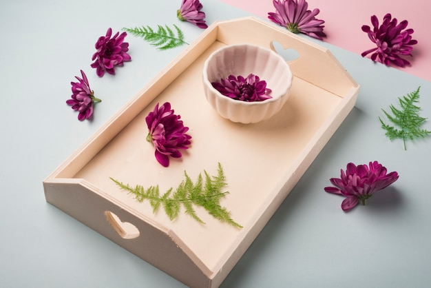Lovely flowers concept with wooden tray