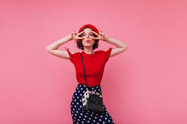 Modello femminile francese adorabile in berretto divertendosi. ritratto dell'interno della donna europea allegra in vestiti rossi.