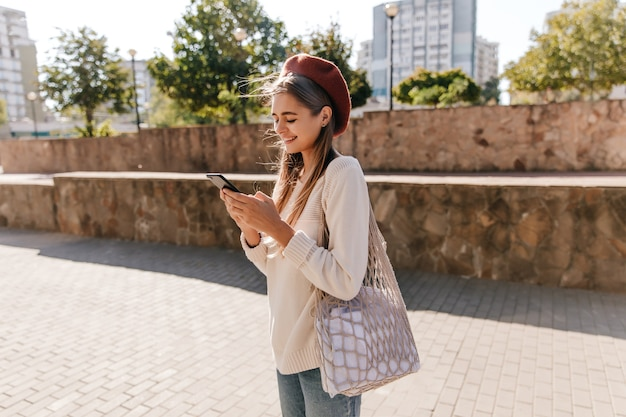 晴れた秋の日に通りに立っているバッグを持つ素敵なフランスの女の子。カジュアルな服装のテキストメッセージメッセージのjocund女性。