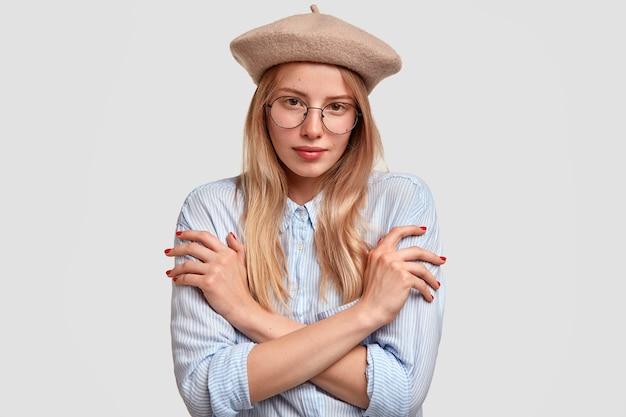 スタイリッシュなベレー帽とシャツを着た素敵なフランス人女性は、手を組んで、白い壁に隔離された表情を予約しています。アイウェアの恥ずかしがり屋の美しい女性が屋内に立っています。美しさと若さ