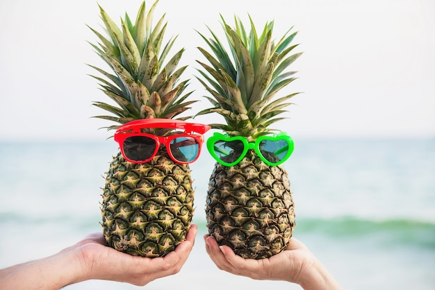 Lovely fresh couple pineapples putting glasses in tourist hands with sea wave - happy love and fun with healthy vacation concept