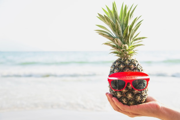 Lovely fresh pineapple putting glasses in tourist hands with sea wave - happy fun with healthy vacation concept