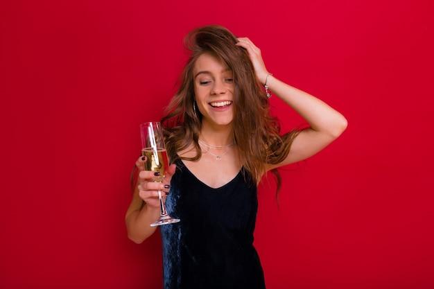 Bella ragazza felice amichevole con lunghi capelli castano chiaro vestita abito da sera blu bere champagne e gli occhi chiusi con vista di piacere divertirsi e trascorrere del tempo durante la celebrazione