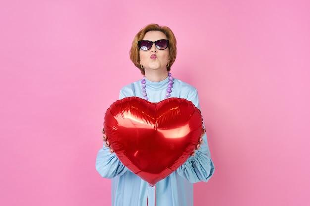 사랑스러운 펑키 늙은 여자가 심장 풍선을 잡고 키스를 불면
