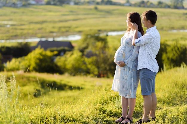 사랑스러운 미래의 부모는 초원에서 걷는다. 행복한 가족과 신생아.
