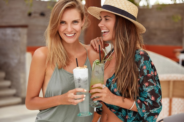 Lovely gay female couple enjoy good recreateion in exotic country, embrace and have good mood, enjoy cold fresh cocktails, wear summer clothing. cheerful woman in straw hat stands near friend