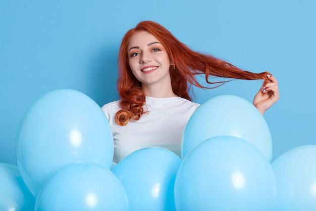 素敵な生姜の女性が誰かとイチャイチャして髪を脇に引っ張り、白いシャツを着て、青い壁に膨らんだ風船でポーズをとる。誕生日パーティー、お祝い。