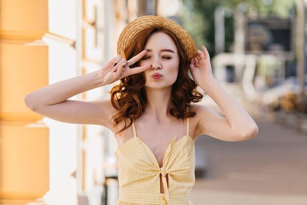 街でキスの表情でポーズをとる黄色のドレスを着た素敵な生姜の女の子。夏の週末を楽しんでいる流行の麦わら帽子の美しい巻き毛の女性。