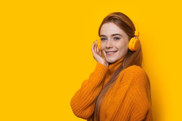 黄色の壁にポーズをとっている間、ヘッドフォンで音楽を聴いているそばかすのある素敵な生姜の女の子
