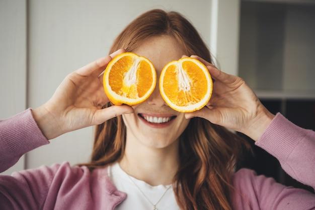 Милая рыжая дама, закрывая глаза нарезанным апельсином, улыбается