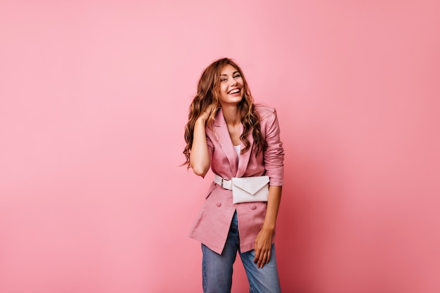 Lovely ginger woman in casual jacket laughing on pink. dreamy young lady in jeans playing with her curly red hair.