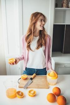 Милая рыжая женщина с веснушками улыбается, нарезая апельсины для приготовления сока ручной соковыжималкой