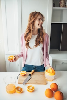 Lovely ginger woman with freckles is smiling while slicing oranges for making juice with a manual squeezer