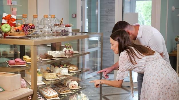素敵な女の子と男は、現代の菓子店のショーケースの棚でデザートを選ぶさまざまなおいしいケーキを見てください