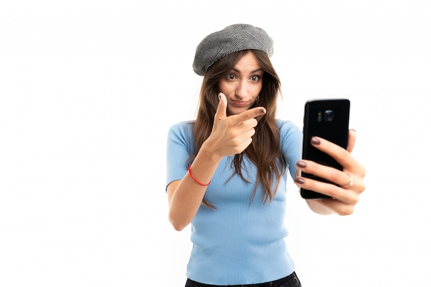 Lovely girl in a beret makes selfie on the phone on a white wall