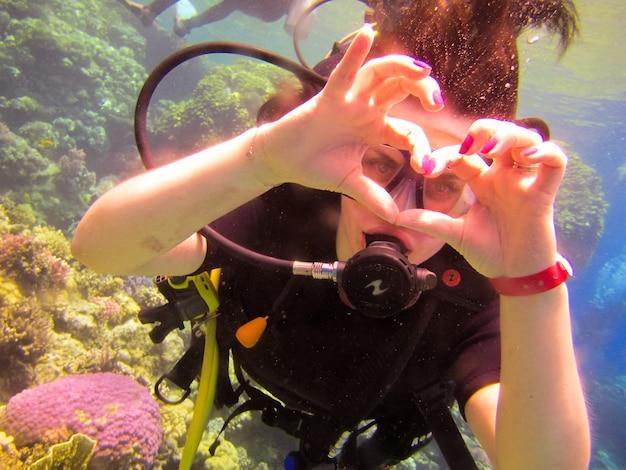 사랑스러운 소녀 다이버는 산호초 이집트, 샤름 엘 셰이크가 있는 홍해에서 안전한 수영을 위해 파트너 강사와 함께 손짓으로 사랑의 표시로 심장을 보여줍니다.