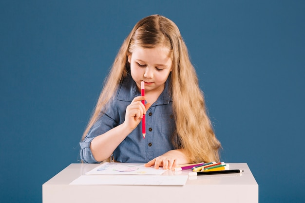 Lovely girl drawing at table