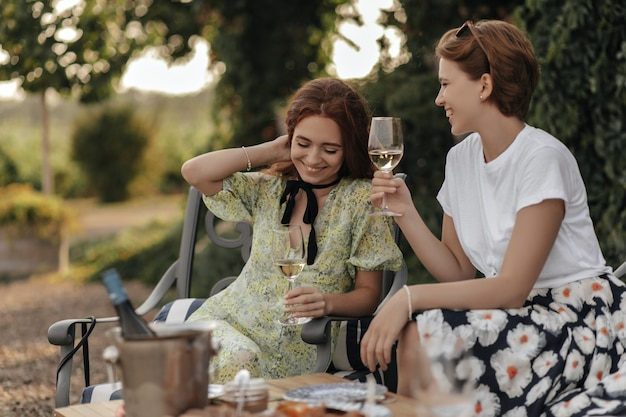Bella ragazza in abiti verdi con in mano un bicchiere di champagne e seduta con una signora in gonna floreale estiva e maglietta leggera all'aperto