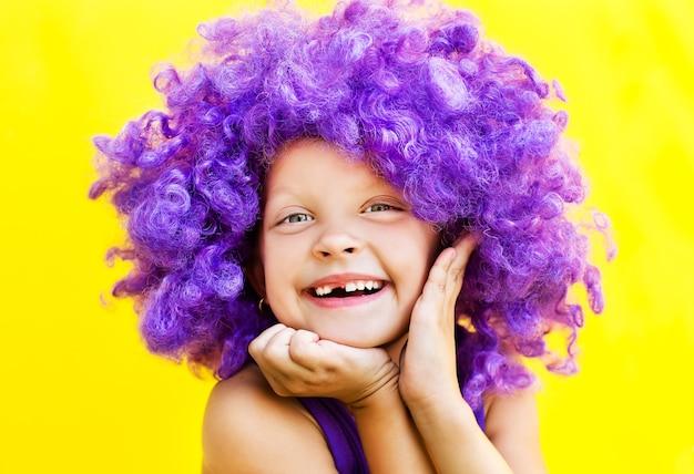 Милая девушка в фиолетовом парике показывает счастливые эмоции