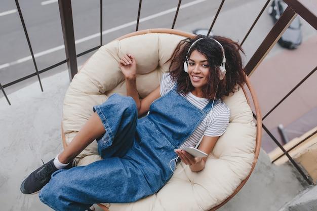 Милая девушка в черных кроссовках лежит в удобной позе на большой подушке и наслаждается музыкой