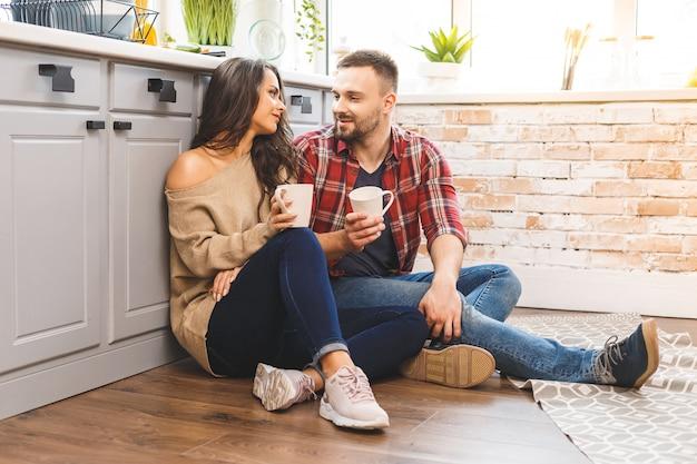 Милая девушка в случайных сидя на полу и разговаривать с парнем. молодая пара, наслаждаясь кофе или чаем в кухне.