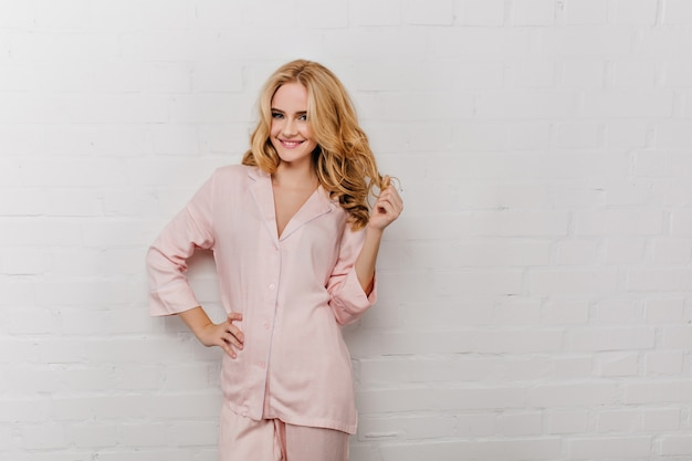 그녀의 물결 모양의 머리를 가지고 노는면 파자마에 사랑스러운 소녀. 핑크 잠 옷 흰 벽에 웃 고있는 웃는 여자의 초상화.