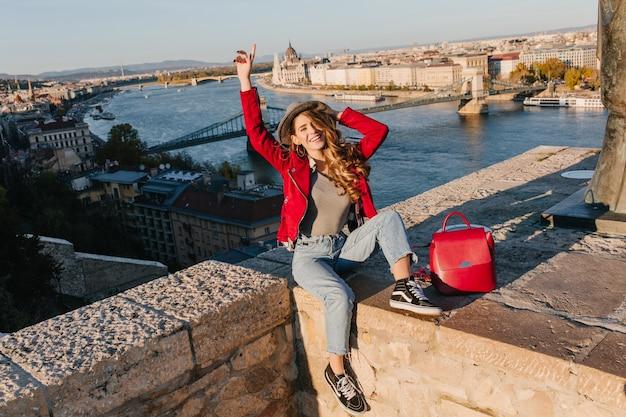 도시 배경에 지붕에 포즈 유행 빨간 재킷에 사랑스러운 소녀