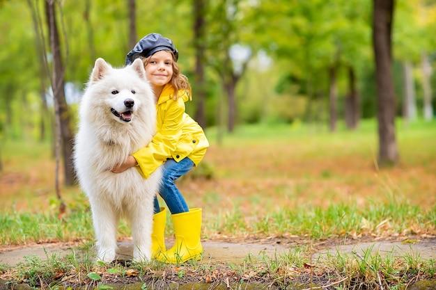 Милая девушка в желтых резиновых сапогах и дождевике на прогулке, играет с красивой белой самоедской собакой в осеннем парке.