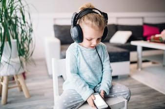 Lovely girl listening to music on chair