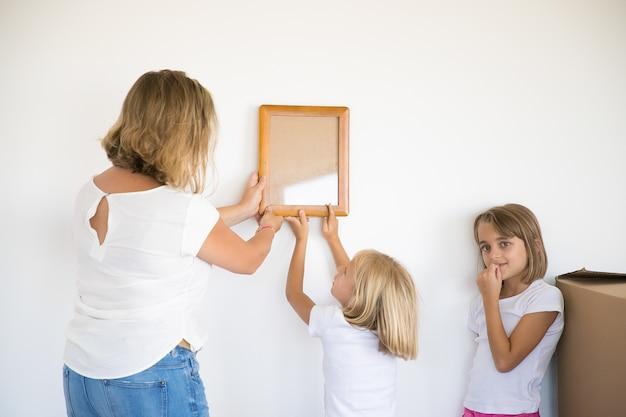 Bella ragazza mettendo cornice sul muro bianco con l'aiuto della mamma
