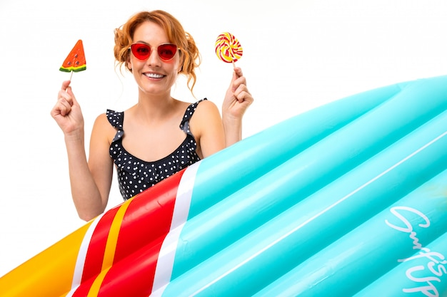 Lovely girl in retro glasses holds two lollipops near an air mattress for swimming