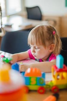 Симпатичная девушка, сидя за столом в игровой комнате