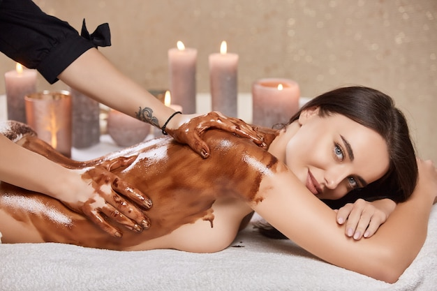 Lovely girl in spa salon having massage with oily chocolate mask and candles