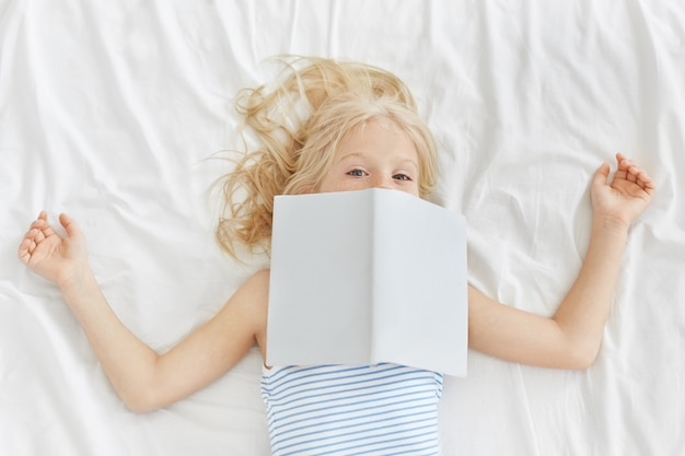 Lovely girl wearing pyjamas, reading fairy tales in bed, covering her face with book.
