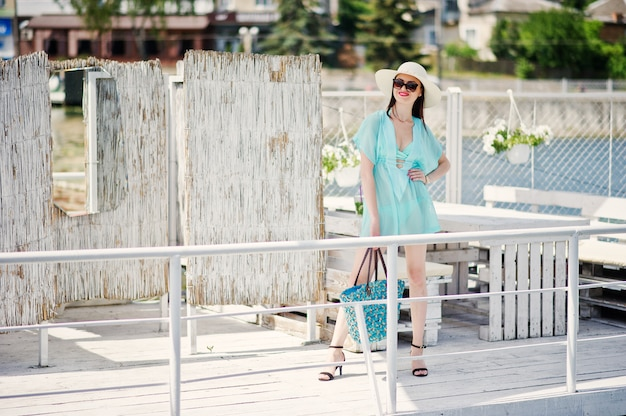 Lovely girl wearing transparent dress, hat and sunglasses walking on the quay by the lake with her bag.