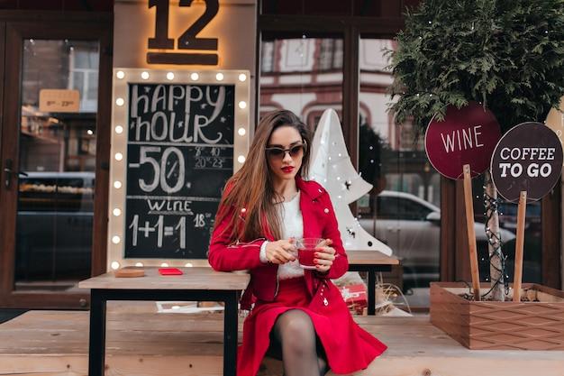 素敵な女の子は、屋外のカフェに座ってサングラスと赤いスカートを着ています