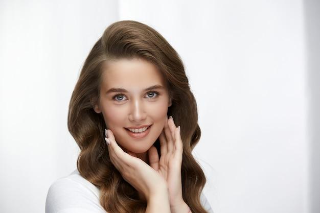 Милая девушка с удивительными вьющимися волосами касается ее лица и смотрит в камеру