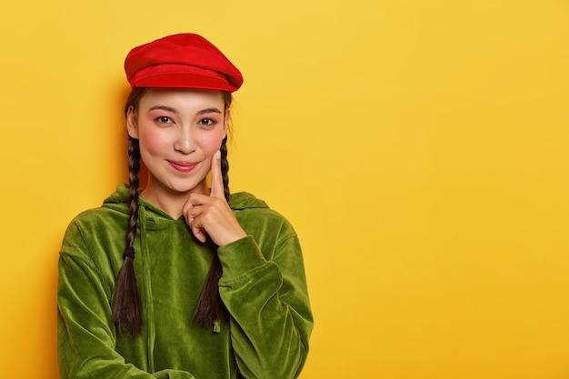 아시아 외모, 최소한의 화장, 검지로 뺨에 닿는 사랑스러운 소녀, 긍정적으로 보이며 쇼핑에 자유 시간을 보내는 것을 즐깁니다.