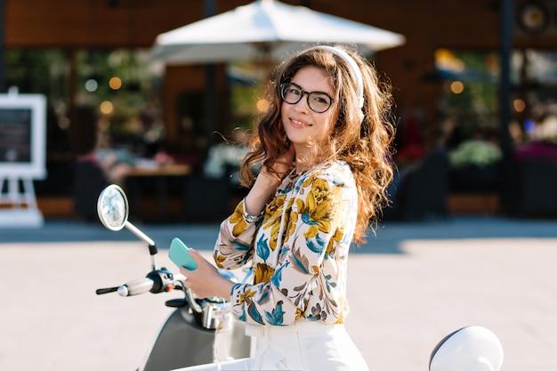 카페 앞에서 친구를 기다리는 동안 관심을 가지고 보이는 아름다운 짙은 갈색 머리를 가진 사랑스러운 소녀