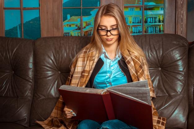 茶色の革のソファの大きな窓に座っている美しい長い髪の素敵な女の子、隠れている毛布と真剣に赤い本を見る