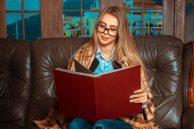 茶色の革のソファの大きな窓に座って、笑顔で赤い本を見ている美しい長い髪の素敵な女の子