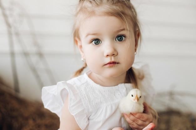 小さなひよこを保つ大きな美しい目を持つ素敵な女の子