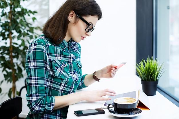 タブレットとコーヒー、フリーランスのコンセプト、クレジットカードの保持、オンラインショッピング、仕事でカフェに座っているシャツと眼鏡を身に着けている黒髪の素敵な女の子。