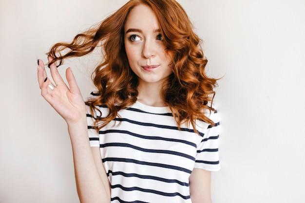 그녀의 물결 모양의 빨간 머리를 가지고 노는 검은 매니큐어와 사랑스러운 소녀. 우아한 헤어 스타일로 평온한 젊은 아가씨의 실내 촬영.