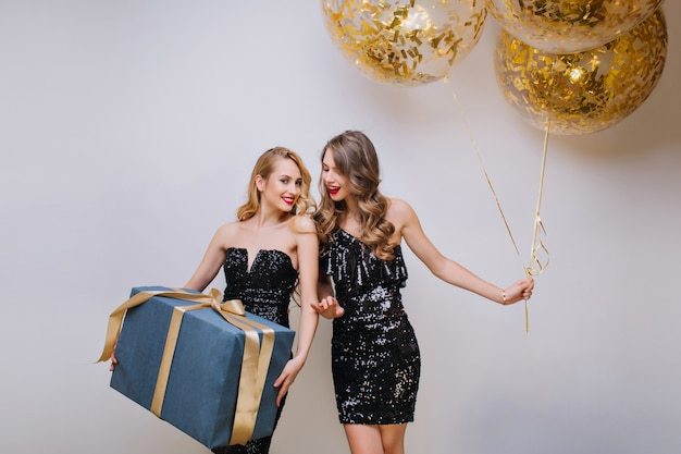Lovely girl with blonde hair posing with pleasure after birthday party. ecstatic caucasian female model with curly hairstyle standing with shining balloons and looking at friend.
