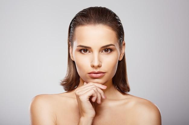 茶色の髪、きれいな新鮮な肌、大きな目と裸の肩を持つ素敵な女の子は、灰色のスタジオの背景でポーズをとっている顔の近くで手をつないでいます。