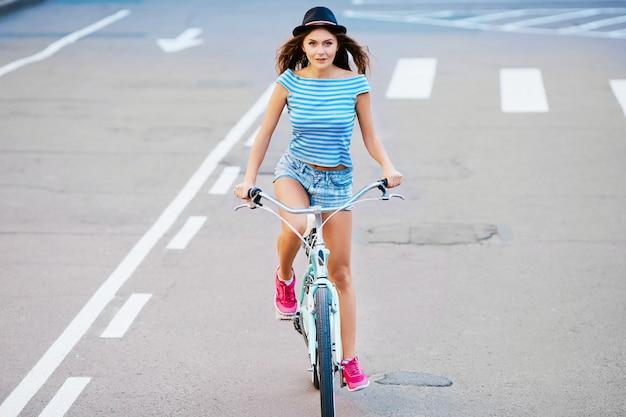 모자, 위쪽 및 공원, 여행, 초상화, 미소, 복사 공간에서 자전거를 타고 반바지를 입고 곱슬 머리를 가진 사랑스러운 소녀.