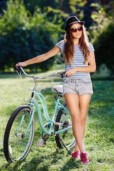 모자, 위쪽 및 공원에서 자전거와 함께 서있는 반바지를 입고, 여행, 초상화, 웃 고 곱슬 머리를 가진 사랑스러운 소녀.