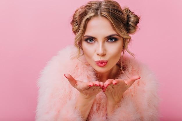 Милая девушка с милой прической и профессиональным макияжем в пушистой шубе посылает воздушный поцелуй. удивительная голубоглазая блондинка смотрит с любовью и позирует, изолированные на ярко-розовом фоне