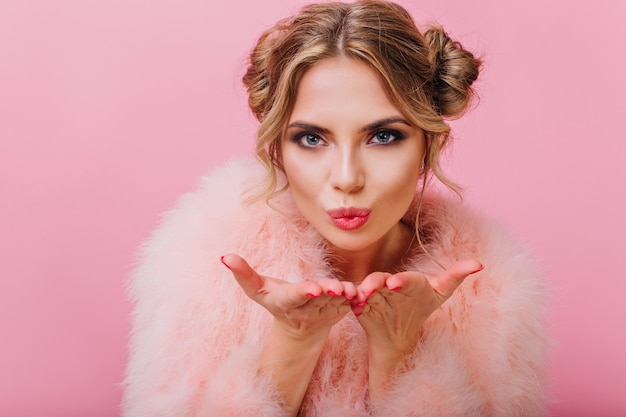 Lovely girl with cute hairstyle and professional make-up in fluffy fur coat sending an air kiss. amazing blue-eyed blonde woman looking with love and posing, isolated on bright pink background